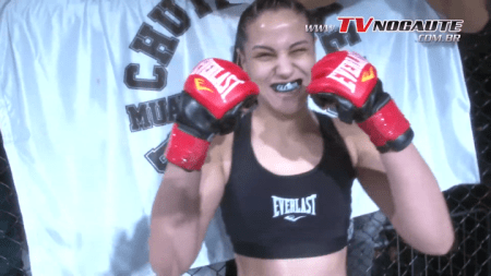 Gloria de Paula shows clenches her fists, which are wearing MMA gloves, at a camera before a fight.