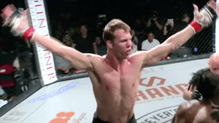 Ryder Newman raises his arms in the air in a celebratory way following a submission win.