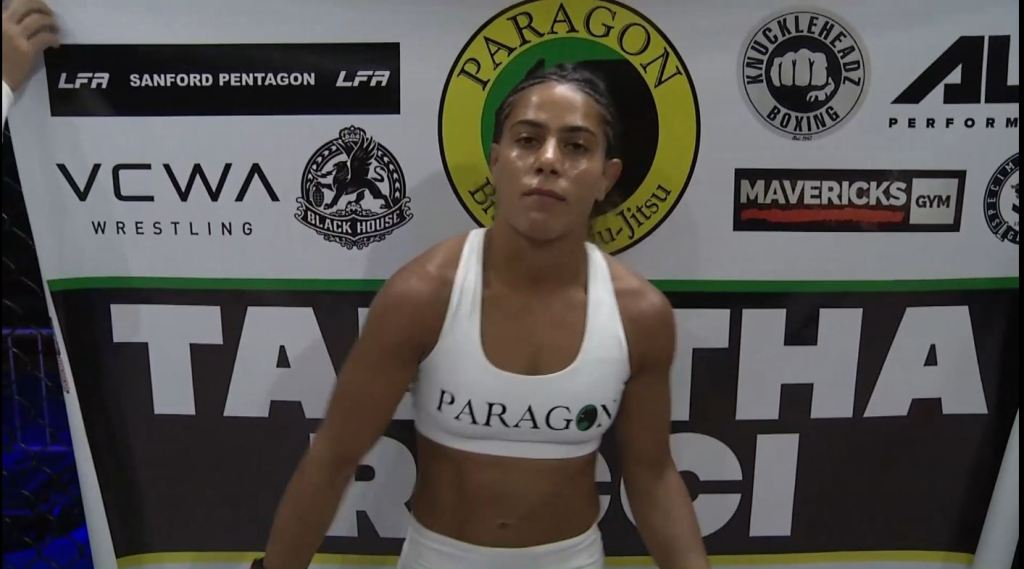Tabatha Ricci stands in an LFA cage while her corner drapes a flag behind her with sponsors.