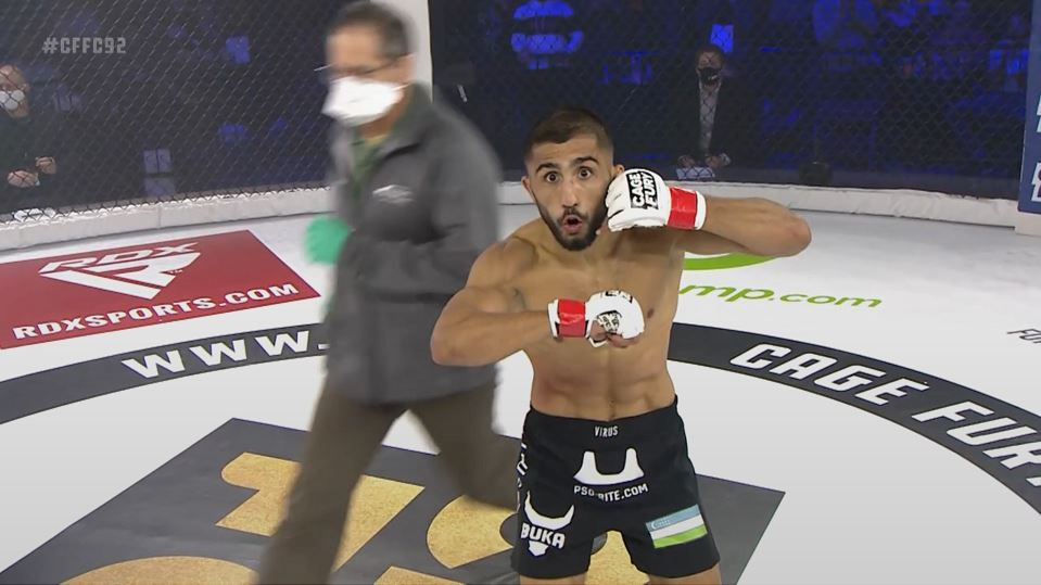 Saidyokub Kakhramonov motions a phonecall movement with his hands while in an MMA cage.