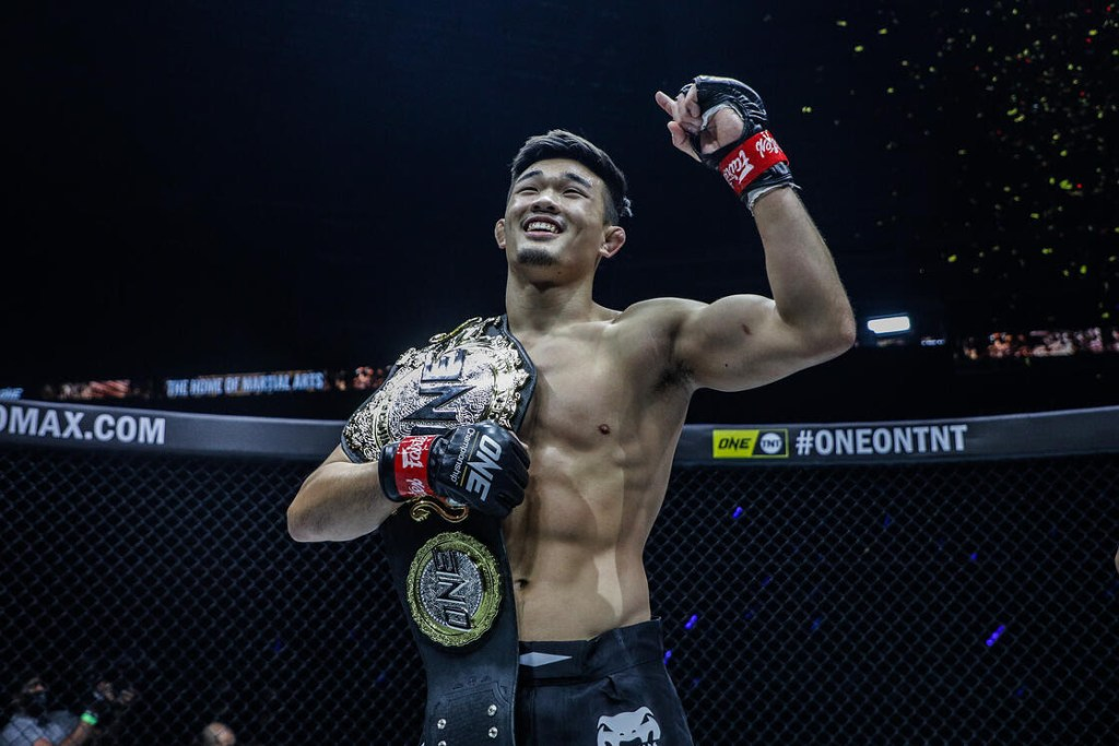 Christian Lee raises his arm while holding a ONE Championship.