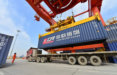 A worker directs container hoisting operation at a logistic station in Xinzhu Railway Station in Xi'an, March 11, 2020.