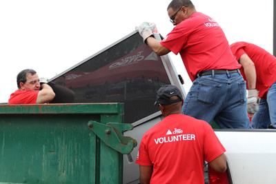 TeamCITGO volunteers load e-waste into roll-off boxes during CITGO E-Recycle Day at the McNeese Cowboy Stadium parking lot.