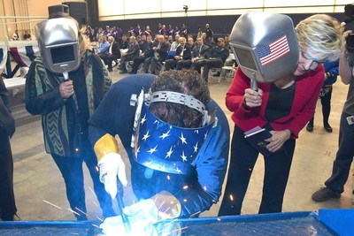A welder authenticates the keel of LCS 25, the future USS Marinette, by welding the initials of ship sponsor Jennifer Granholm.