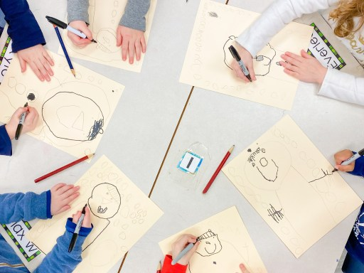 Students tracing their artwork in black marker after a directed drawing lesson