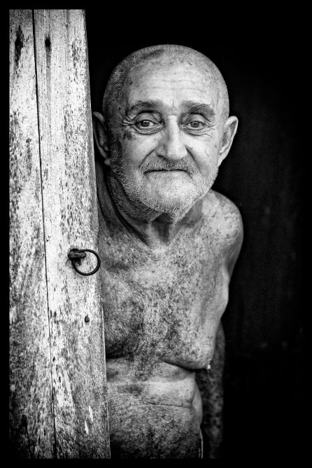 _E7A9478 Man with no shirt standing in doorway Trinidad B&W web ready