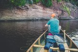 Man fishing from a canoe on the St. Louis River by rock ledge