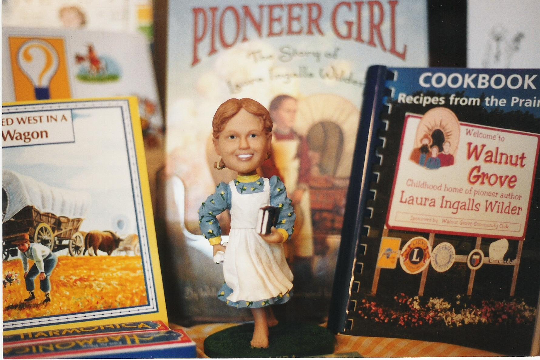 A Laura Ingalls bobblehead and related books for sale at a Walnut Grove gift shop.