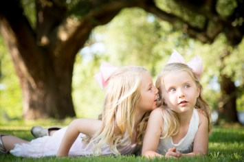 Twin sisters tell secrets under oak trees