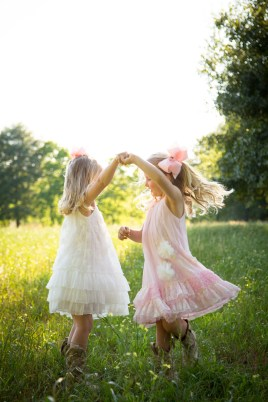 Twin sisters dance in a meadow