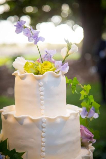 Fresh flowers top a ruffled wedding cake