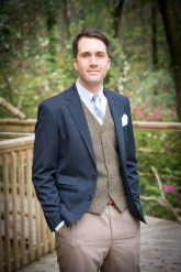 A groom in a navy sport coat and tweed vest