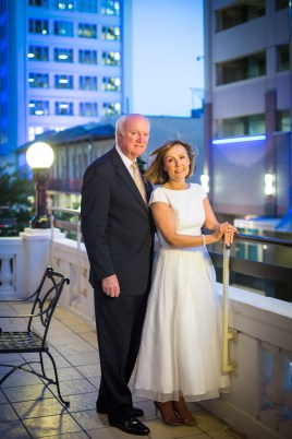A bride and groom on the balcony overlooking Mobile, Alabama