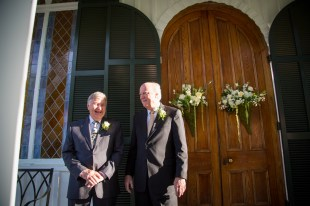 Old friends laugh at the church door