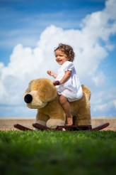 A toddler rides a rocking horse.