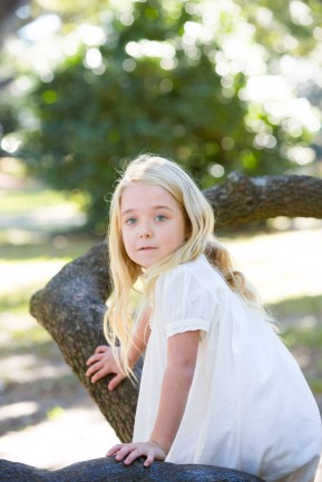 A blonde girl in a white dress climbs the limbs of a live oak tree