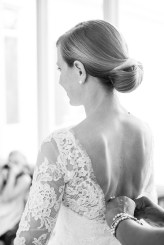 Buttoning the bride's elegant wedding dress