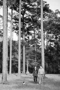A happy couple walks their dog through a meadow of pine trees in Alabama
