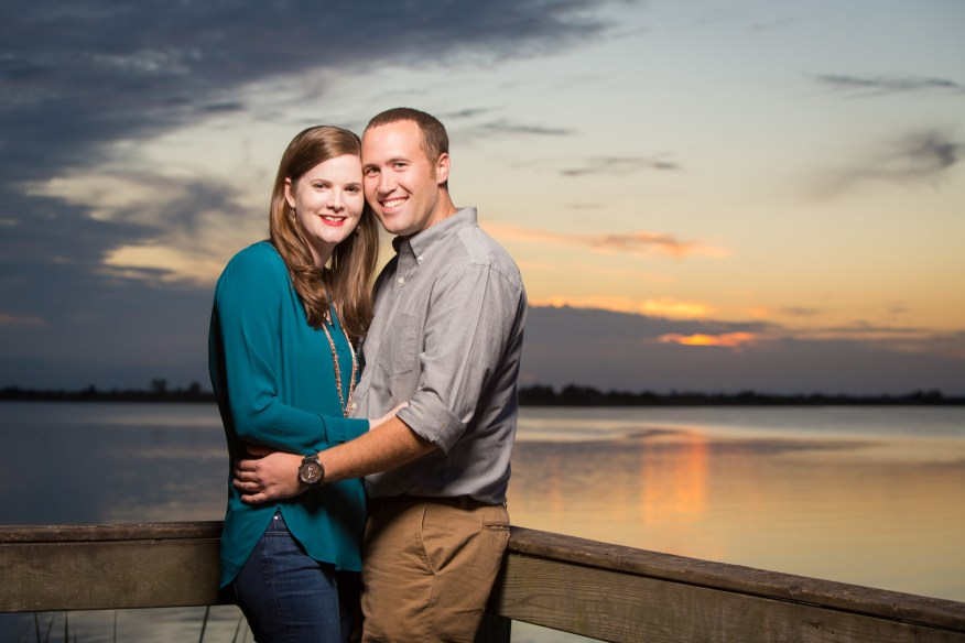 A young couple embraces as the sun sets over the water