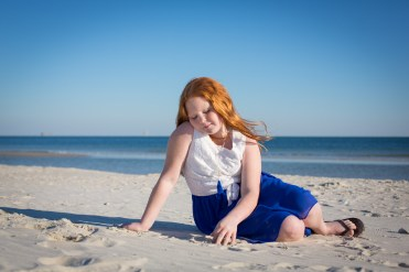Beautiful red-headed girl spends a quiet moment on the beach in Alabama