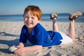 Ginger-headed boy with seashell on the Gulf of Mexico