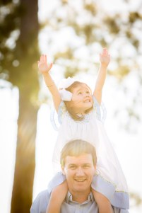 Little girls reaches for the sky atop Daddy's shoulders