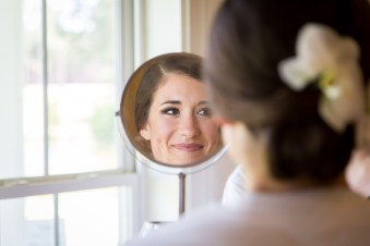 Bride sees her reflection after hair and makeup at Blackwater Farms in Loxley, Alabama