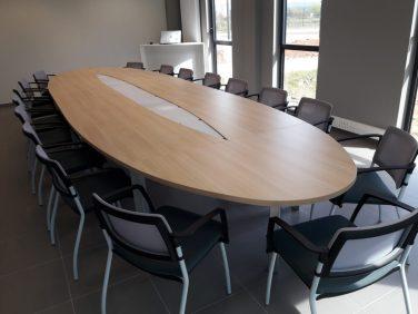 Salle de réunion elliptique Modulo 8 en mélaminé coloris chêne clair et piètement gris alu. Connexions multimédia au centre de la table sous les plaques en Altuglass amovibles.