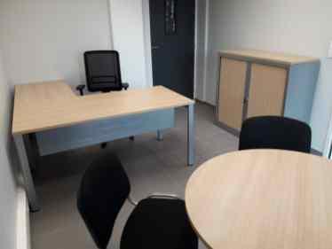 Bureau Arial avec plateau en coloris chêne clair et piètement gris alu. Table de réunion avec 4 sièges visiteurs noirs.