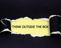 Think Outside The Box appearing behind black torn paper.