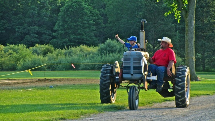 Father and son enjoying a ride on an old tractor