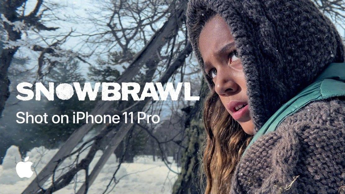 """Kadr z reklamy iPhone'a 11 pt. """"Snowbrawl"""" przedstwaijący dziewczynke z kapturem (napis na grafice: SNOWBRAWL – Shot on iPhone 11 Pro"""""""