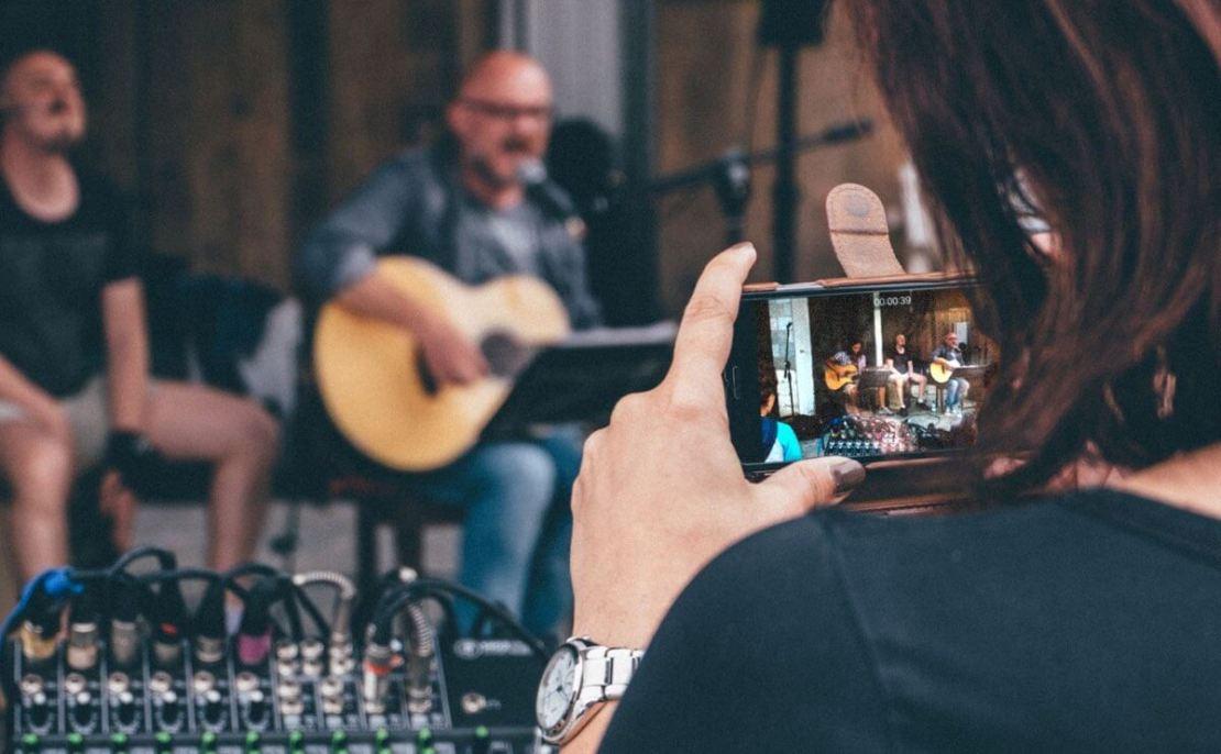 Kobieta nagrywająca smartfonem wideo koncertu