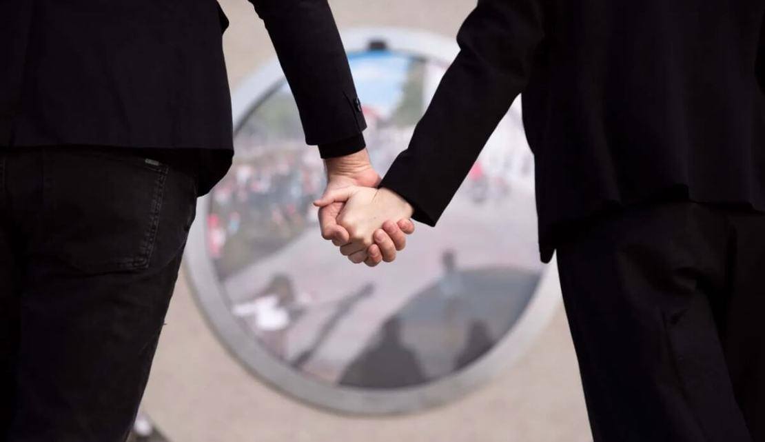 Para trzymająca się za ręce przed portalem w Wilnie