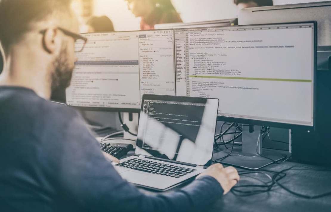 programista przed komputerem