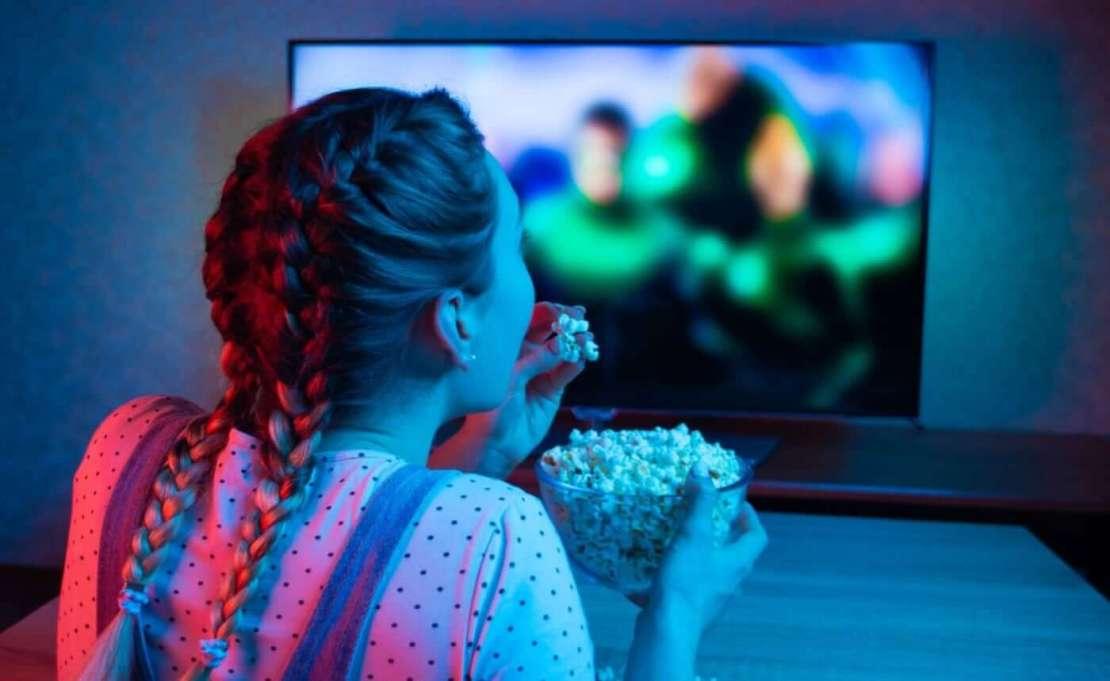 Dziewczyna z popcornem siedząca przed telewizorem