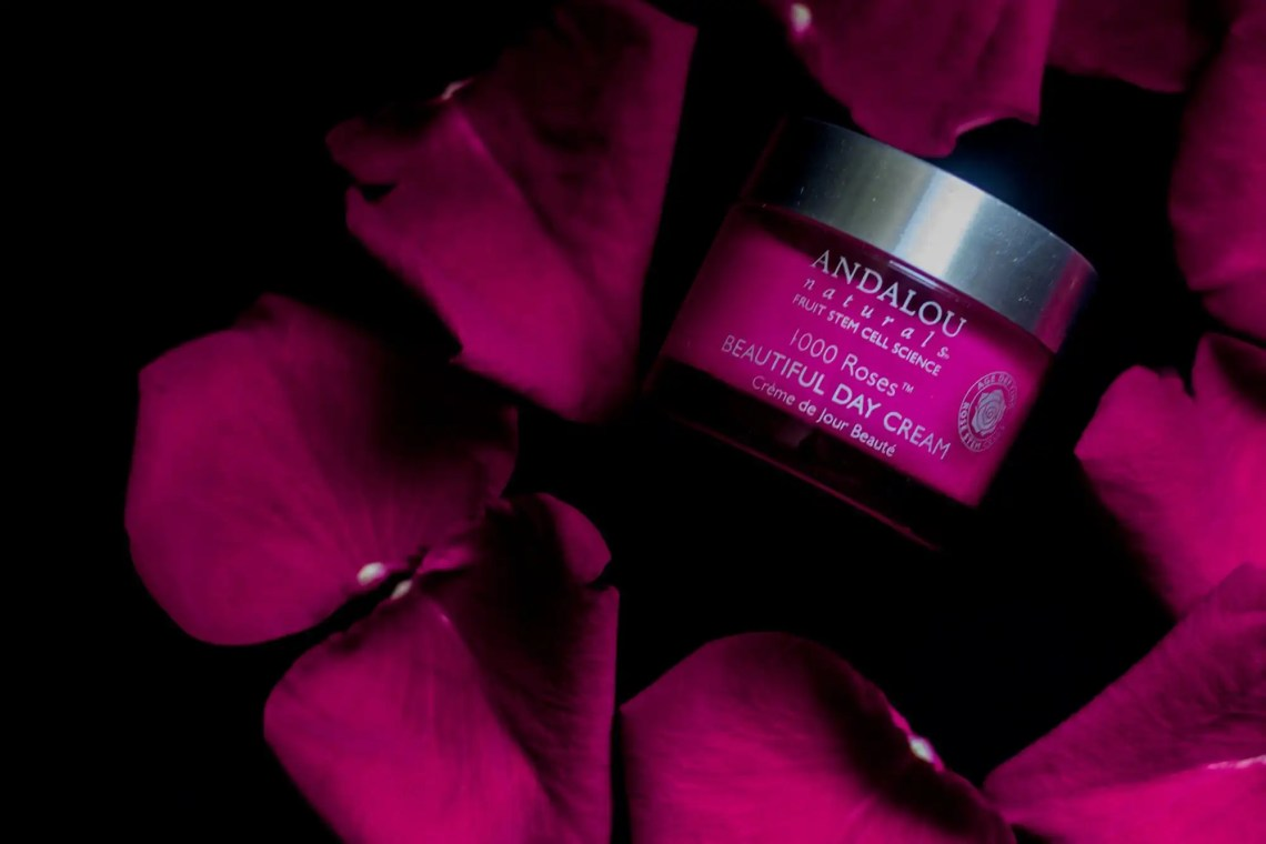 Andalou Naturals day cream jar on a bed of roses