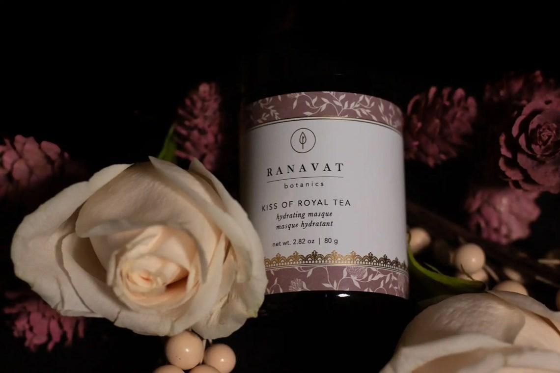 Ranavat Botanics Kiss of Royal Tea masque jar set next to white flowers and black background