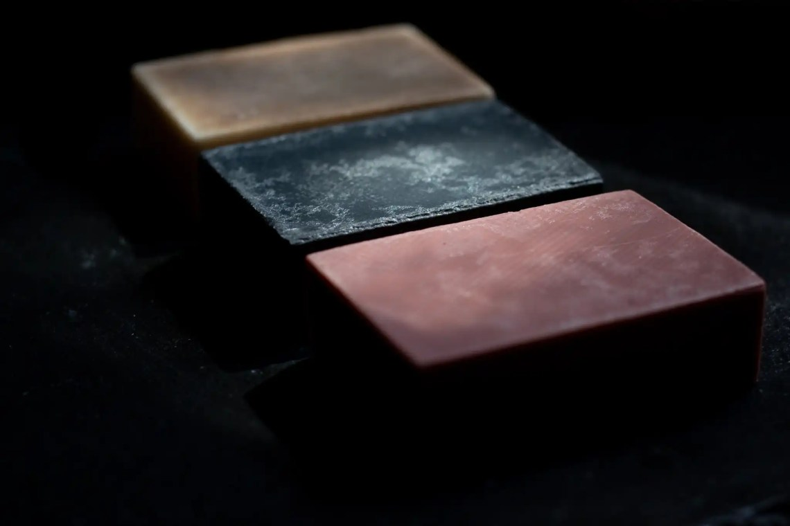 three bar soaps in pink, gray, and cream on a dark background