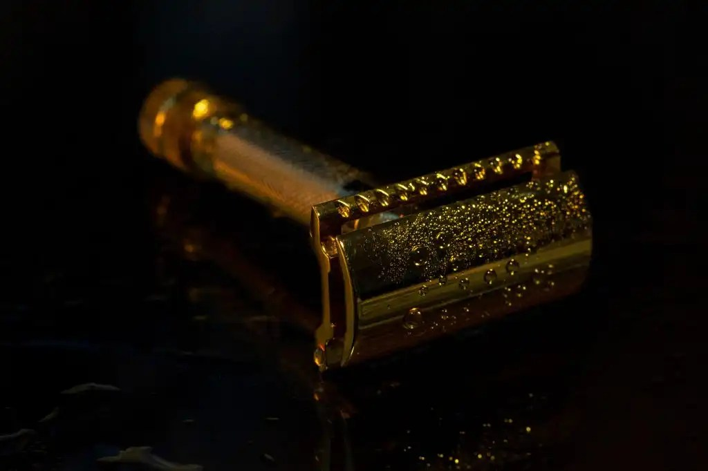 gold safety razor with water droplets on black background