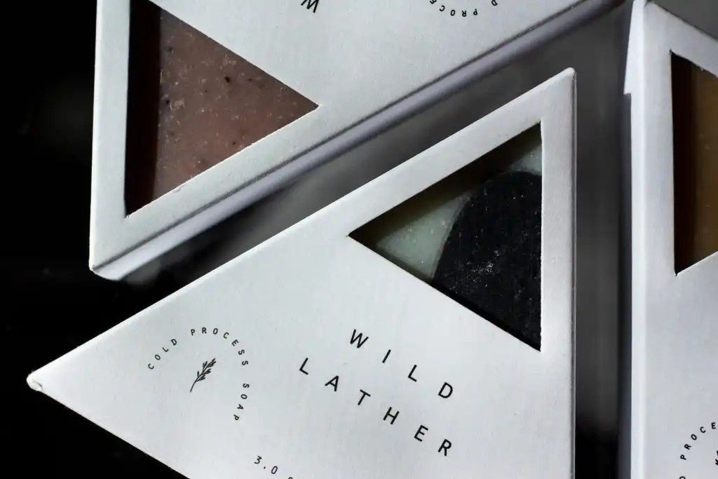 Women-owned beauty brand Wild Lather white triangle shaped soaps on a black background