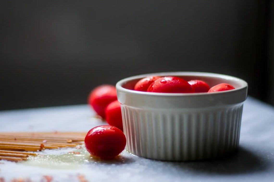 Red grape tomatoes in a ramekin on a marble board