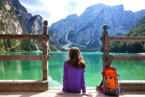mochilera con su mochila a orillas de un lago en los Dolomitas, Italia