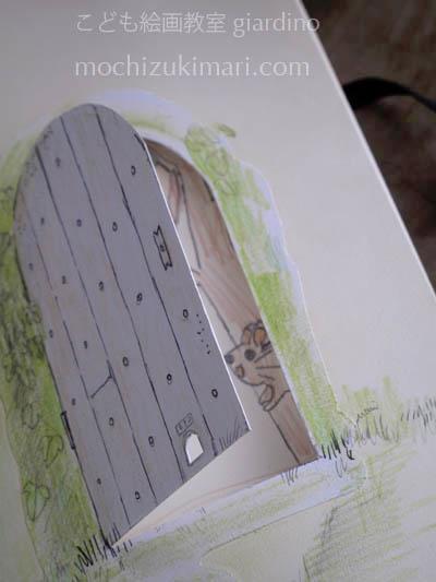 鎌倉こども絵画教室giardino 受講者 モレスキン作品。モレスキンの一番はじめのページに仕掛け扉を作り、受講生は当時のペットのハムスターを見えるように構成し描いてくれた。次の回で私はハムスターの入り口を扉に開けて応じた。