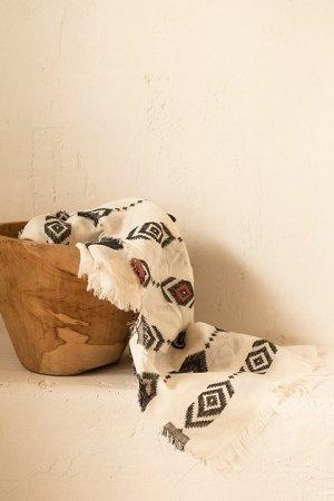 Chal de bordado étnico con detalles de color, fondo ecru.