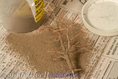 In den feuchten Kleber sogleich feinen Sand streuen.