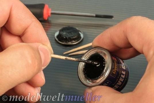 Mit einem Zahnstocher wird die Farbe möglichst ohne Öl vom Grund der Dose hervorgeholt.