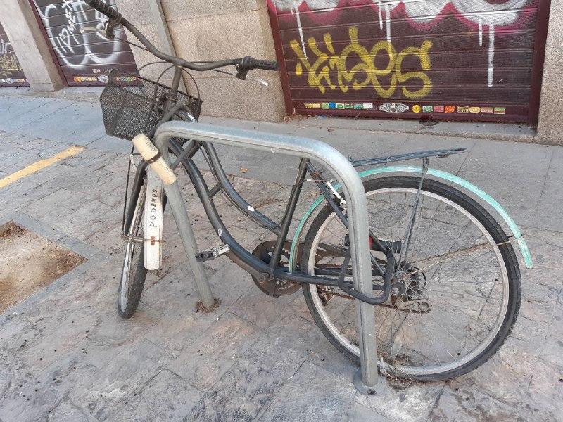 Bicicleta abandonada y vandalizada en un aparcabicis de Madrid.