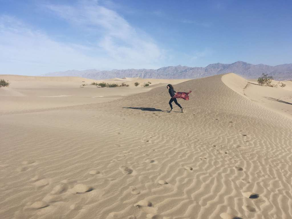 Girl running with scarf, Mesquite Flat Sand Dunes, Death Valley National Park, California