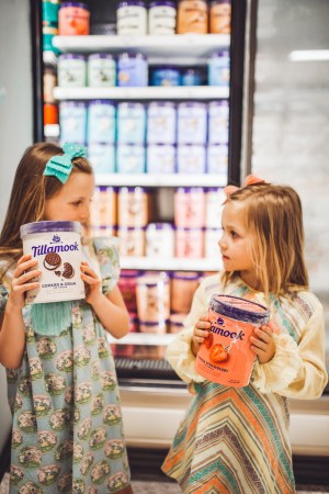 How to Throw a Fun and Easy Summer Soiree by popular Nashville blog Modern Day Moguls: image of two young girls each holding a carton of Tillamook ice cream in the frozen food aisle at Publix grocery store.